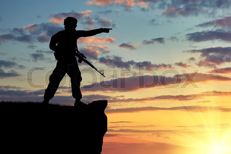 Stock image of 'Silhouette of soldier with a gun on a background of sunset'