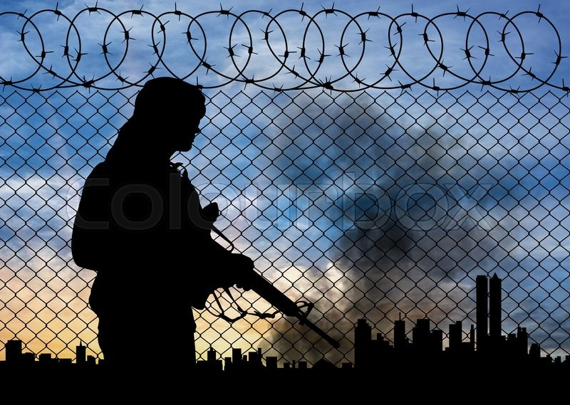Stock image of 'Concept of terrorism. Silhouette terrorists near the border fence in the background on the city in smoke at sunset'