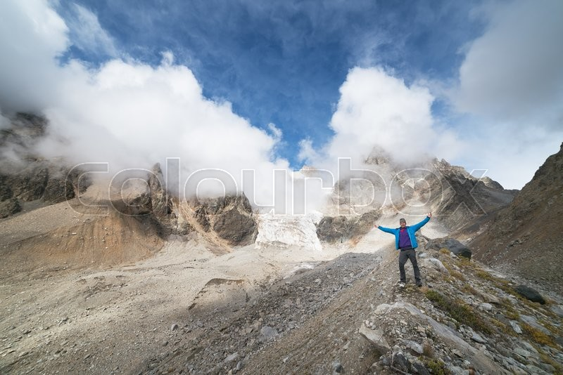 Stock image of 'Mountain landscape. Tourist standing on the crest of the ridge. Mountain glacier. Beauty in nature. Hiking on the mountain peaks. Caucasus, Georgia, Zemo Svaneti'