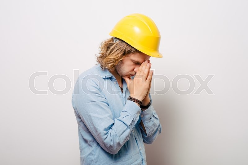 Stock image of 'Construction worker praying'
