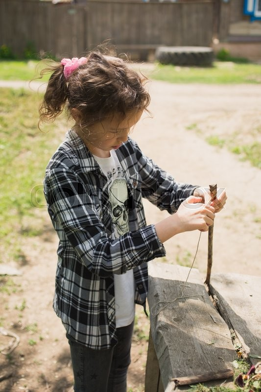 Stock image of 'eight-year-old girl in a plaid shirt plays one on the street with a rope and a wooden stick in the village during summer'