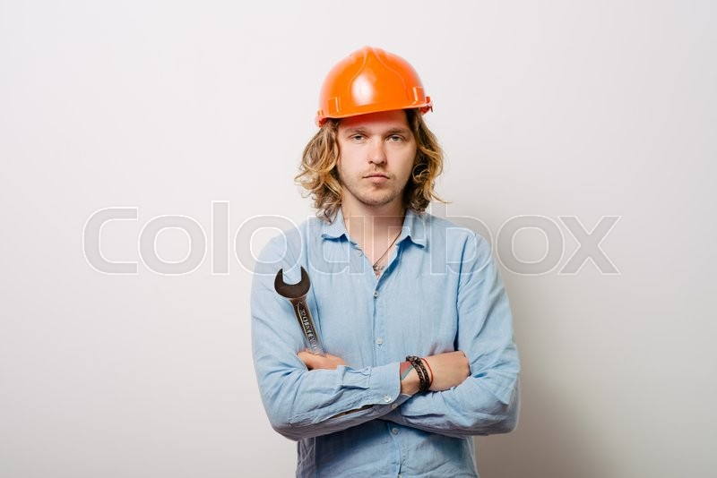 Stock image of 'Portrait of young handyman holding a wrench'