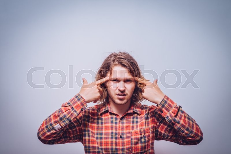 Stock image of 'Closeup portrait of angry man gesturing with his finger against his temple, are you crazy?'