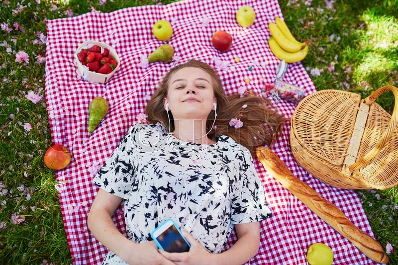 Stock image of 'Beautiful young woman having picnic in parc, lying on her back with fruits around her, listening to the music. View from above. Relaxing or studying in park concept'