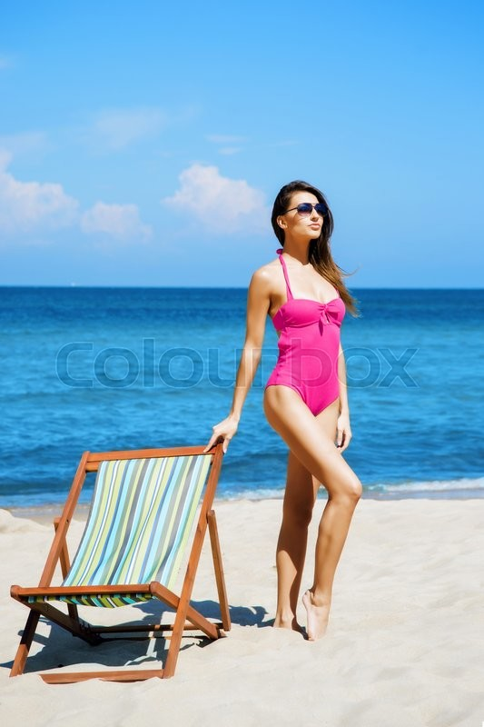 Stock image of 'Young, sporty, beautiful and happy woman relaxing on a summer beach'