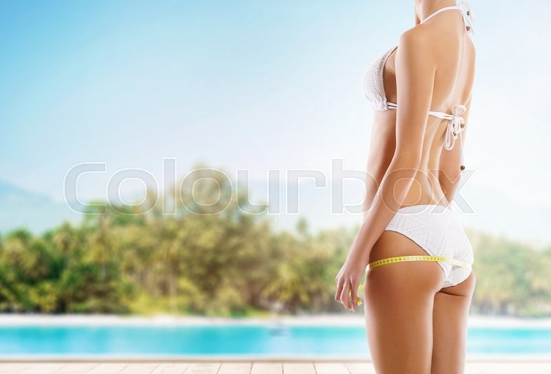Sexy girl measuring perfect body. Summer beach background. Fat lose, sport and fitness concept, stock photo