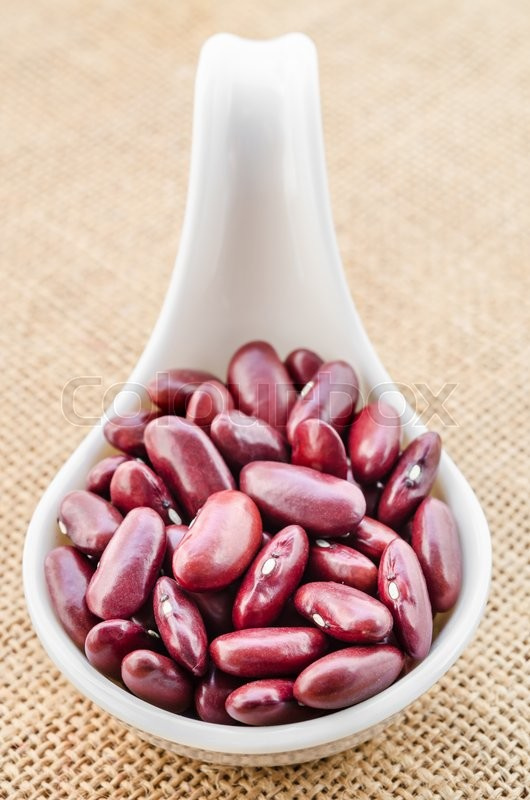 Stock image of 'Portion of dried red beans in white spoon on sack background.'