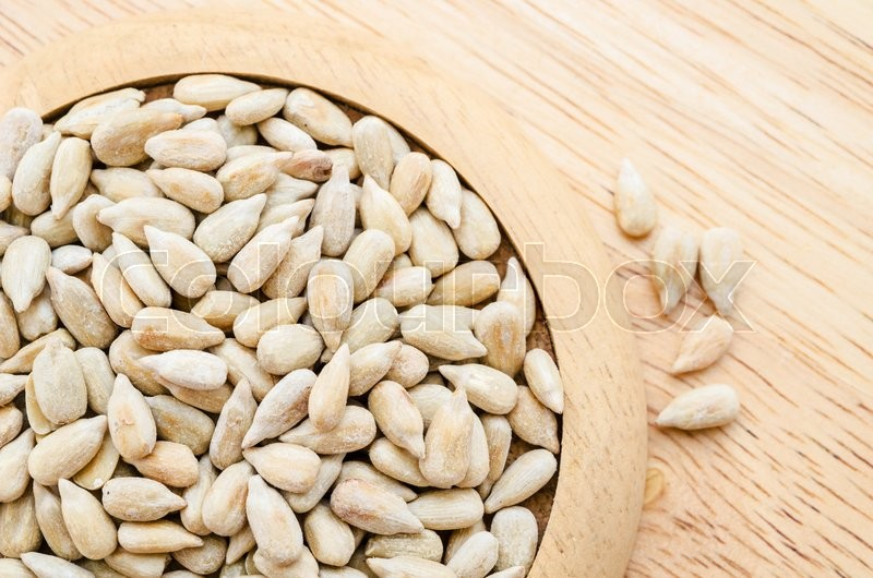 Stock image of 'Sunflower seeds in wooden dish on wooden background.'