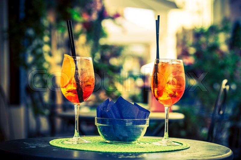 Stock image of 'Aperol Spritz Cocktail. Alcoholic beverage based on table with ice cubes and oranges.'