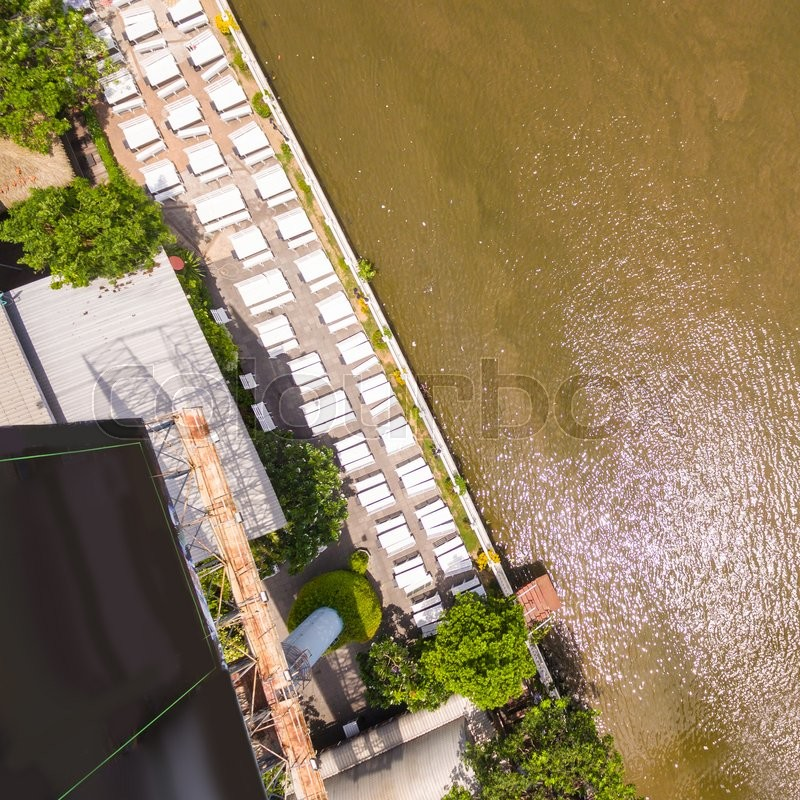 Aerial view Restaurant with wooden tables and chairs placed at the waterfront, stock photo
