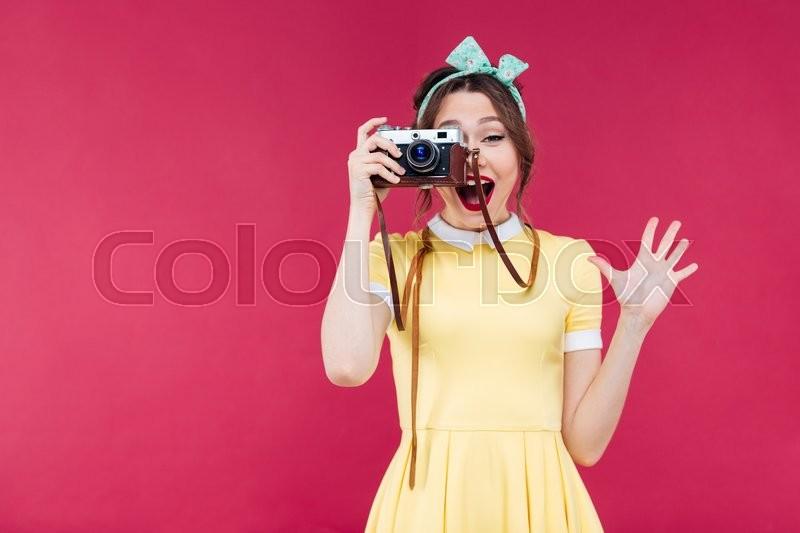 Stock image of 'Happy pretty pinup girl in yellow dress taking pictures with vintage camera over pink background'