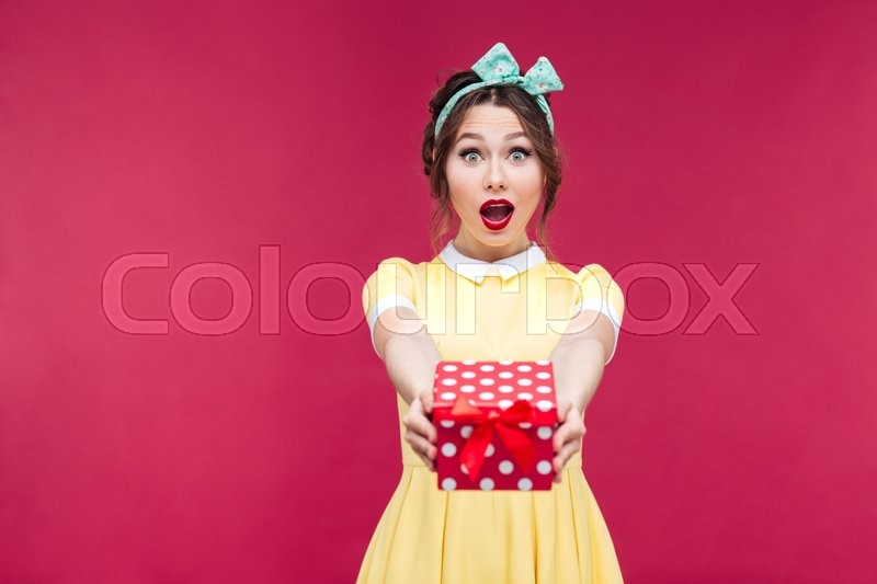 Happy surprised young woman giving you a gift box over pink background, stock photo