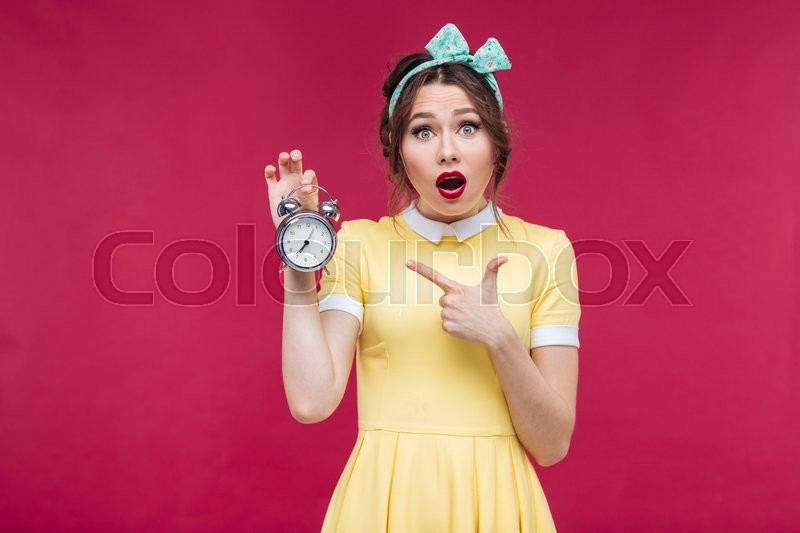 Stock image of 'Cute amazed pinup girl pointing on alarm clock over pink background'