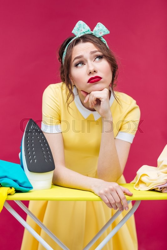 Stock image of 'Thoughtful unhappy pinup girl ironing clothes over pink background'
