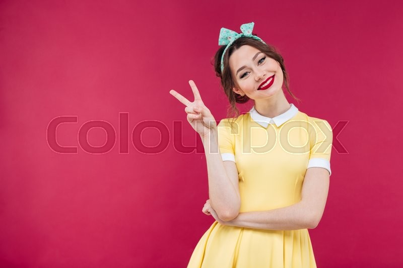 Stock image of 'Smiling charming young woman in yellow dress showing peace sign over pink background'
