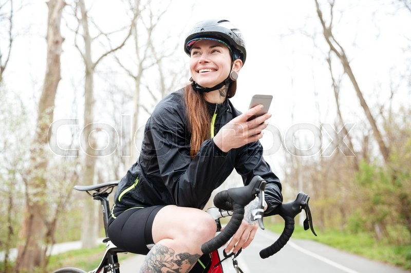 Stock image of 'Happy attractive young woman in cycling helmet on bicycle using smartphone'