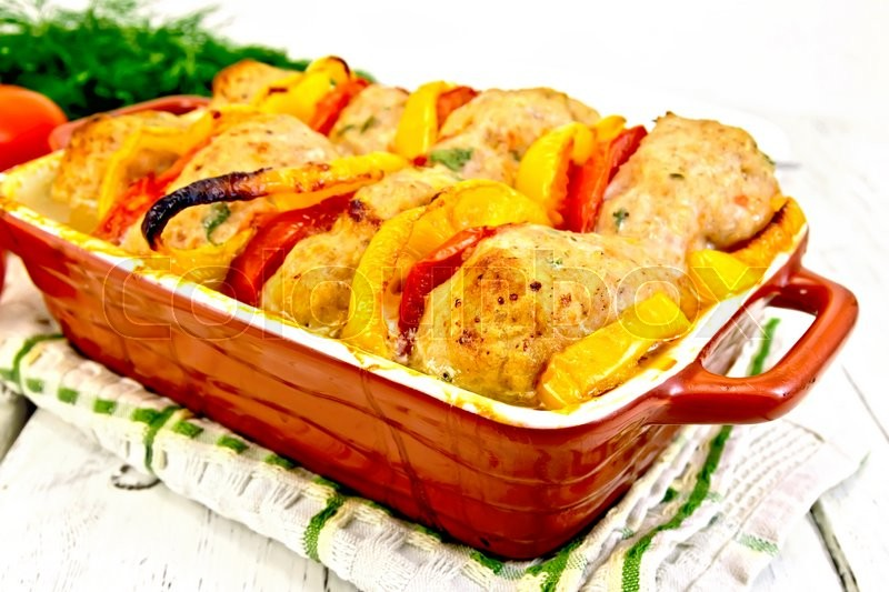 Stock image of 'Cutlets of turkey meat baked with red tomatoes and yellow pepper in a ceramic roasting pan on a towel, parsley on a wooden boards background'