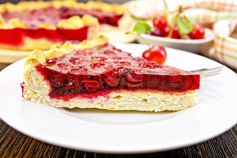 Stock image of 'Piece of sweet pie with cherries and jelly in a plate with a fork on the background of wooden boards'