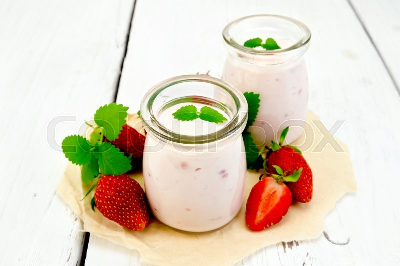 Stock image of 'Yogurt with strawberries in two glass jars, strawberry and mint on a parchment background on wooden board'