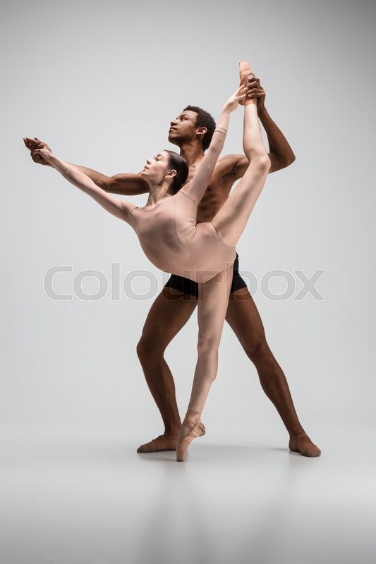Stock image of 'Couple of ballet dancers dancing over gray background'