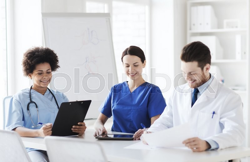 Stock image of 'hospital, profession, people and medicine concept - group of happy doctors with tablet pc computers meeting at medical office'