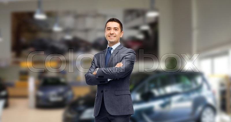 Stock image of 'auto business, car sale and people concept - happy smiling businessman or dealer in suit over auto show background'