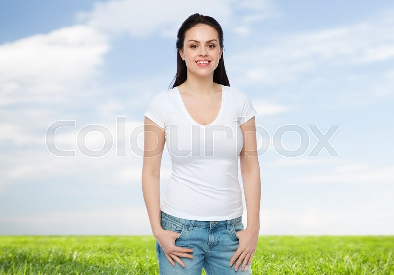 Stock image of 'advertisement, clothing and people concept - happy smiling young woman or teenage girl in white t-shirt over blue sky and grass background'