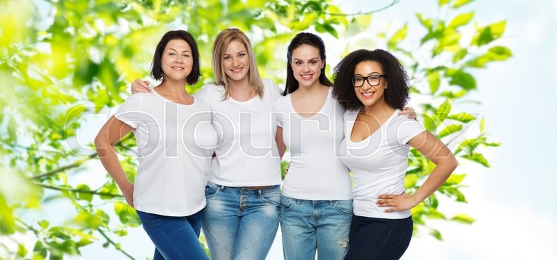 Stock image of 'friendship, diverse, body positive and people concept - group of happy different size women in white t-shirts hugging over green natural background'
