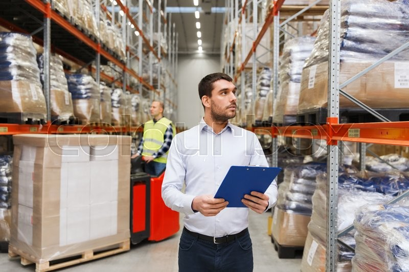 Stock image of 'wholesale, logistic, people and export concept - businessman with clipboards at warehouse'