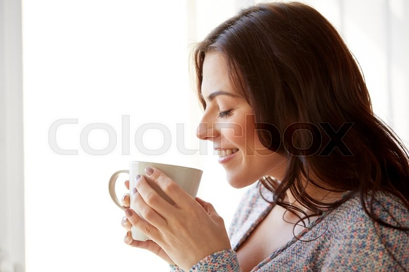 Stock image of 'people, drinks and leisure concept - happy young woman with cup of tea or coffee at home'