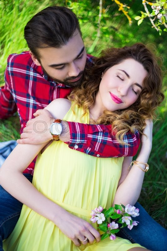 Stock image of 'young man embracing his girlfriend in summer garden'