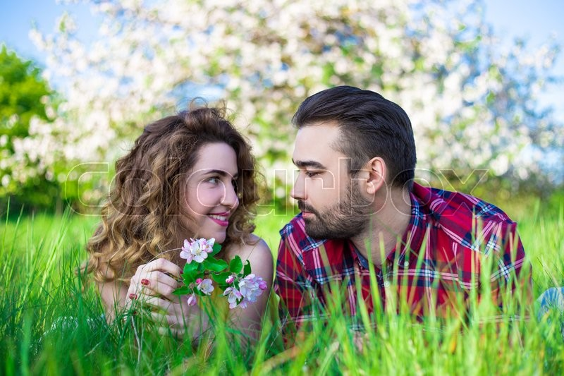 Stock image of 'young beautiful couple lying and talking in summer park'