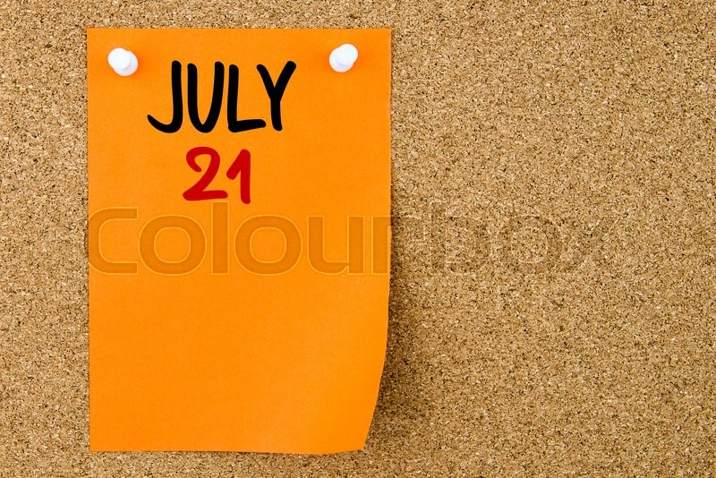 Stock image of '21 JULY written on orange paper note pinned on cork board with white thumbtacks, copy space available'