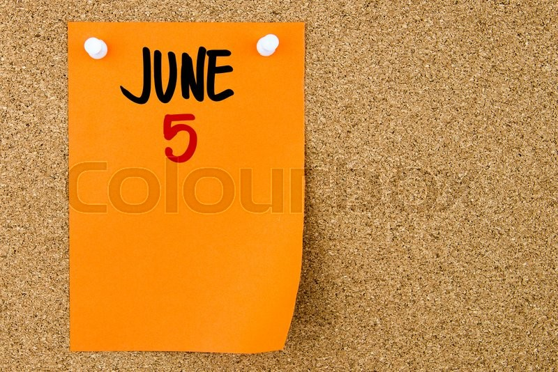 Stock image of '5 JUNE written on orange paper note pinned on cork board with white thumbtacks, copy space available'
