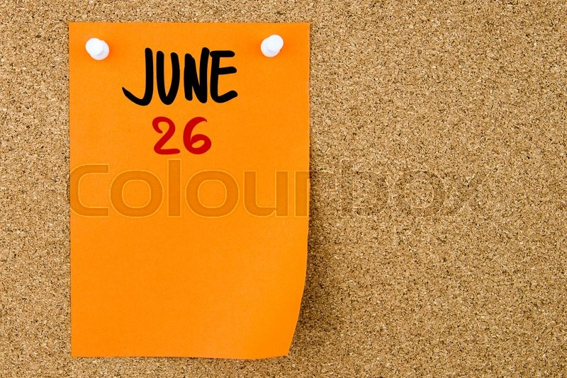 Stock image of '26 JUNE written on orange paper note pinned on cork board with white thumbtacks, copy space available'