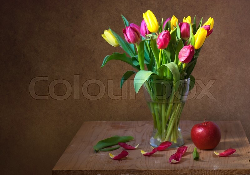 Stock image of 'Still life with red and yellow tulips and red apple on wooden table'