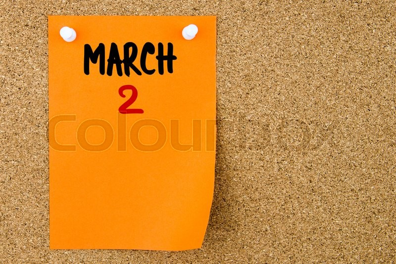Stock image of '2 MARCH written on orange paper note pinned on cork board with white thumbtacks, copy space available'