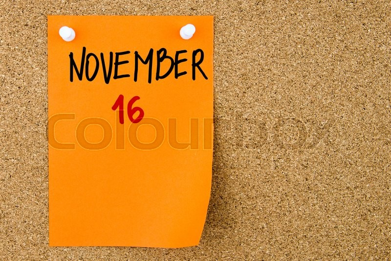 Stock image of '16 NOVEMBER written on orange paper note pinned on cork board with white thumbtacks, copy space available'