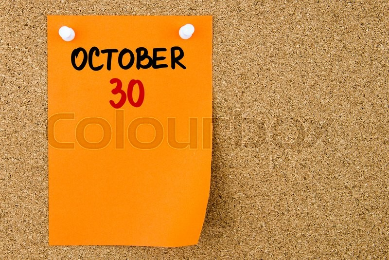 Stock image of '30 OCTOBER written on orange paper note pinned on cork board with white thumbtacks, copy space available'
