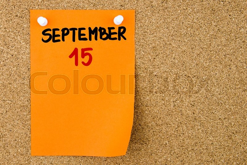 Stock image of '15 SEPTEMBER written on orange paper note pinned on cork board with white thumbtacks, copy space available'