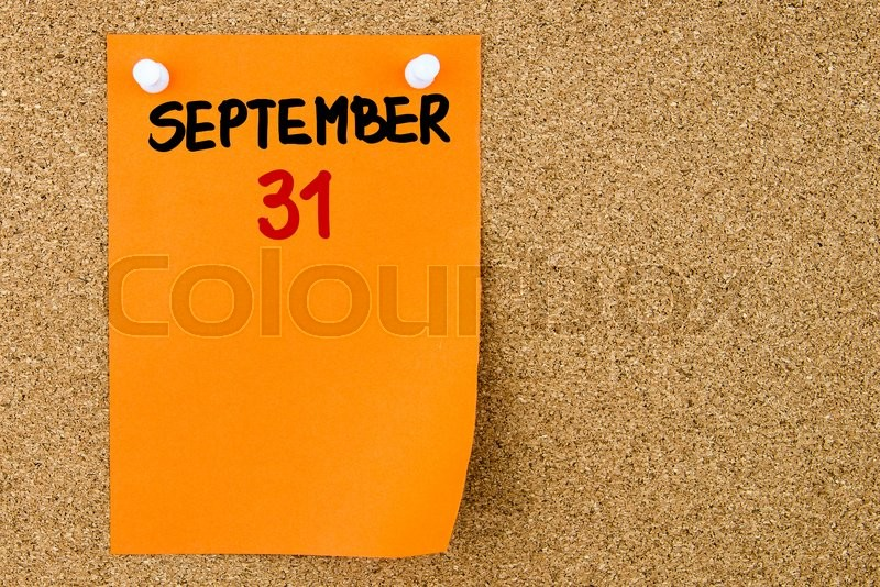 Stock image of '31 SEPTEMBER written on orange paper note pinned on cork board with white thumbtacks, copy space available'