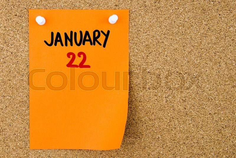 Stock image of '22 JANUARY written on orange paper note pinned on cork board with white thumbtacks, copy space available'