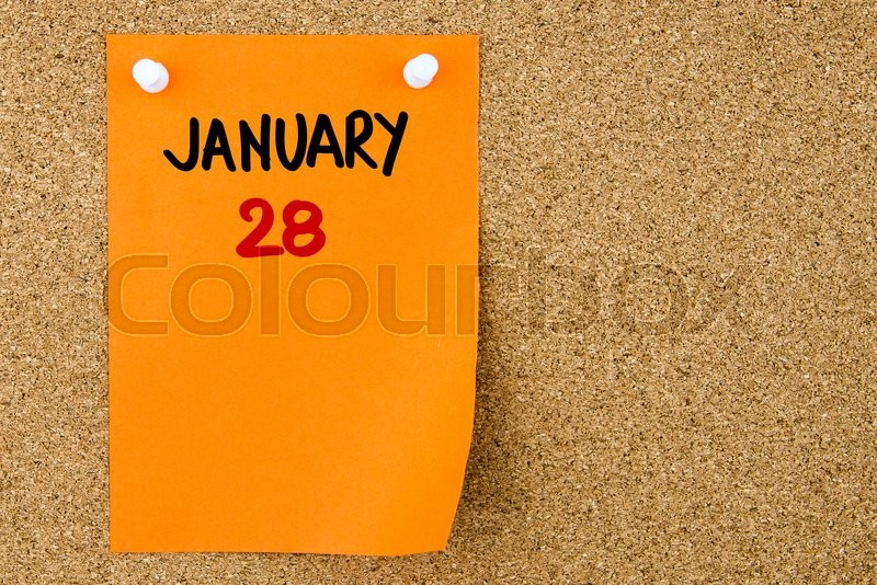 Stock image of '28 JANUARY written on orange paper note pinned on cork board with white thumbtacks, copy space available'
