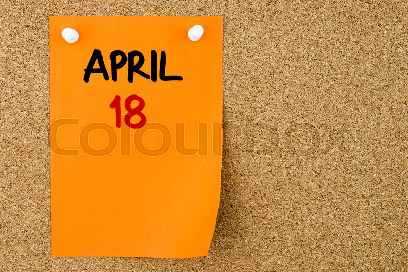 Stock image of '18 APRIL written on orange paper note pinned on cork board with white thumbtacks, copy space available'