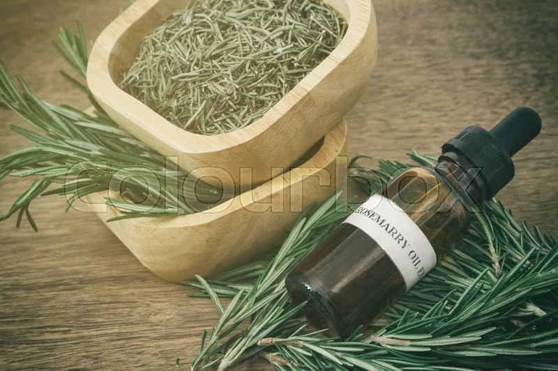 Stock image of 'Rosemary essential oil in bottle and fresh rosemary on old wooden background'