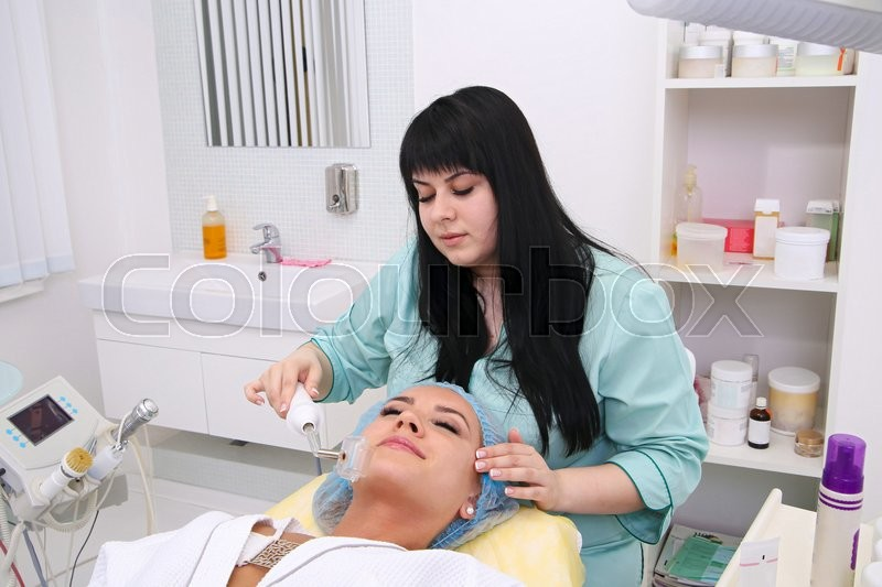 Stock image of 'People, beauty, spa, cosmetology and technology concept - close up of beautiful young woman lying with closed eyes having face massage by massager in spa.'