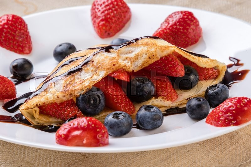 Stock image of 'fresh pancake with fruits and chocolate syrup'