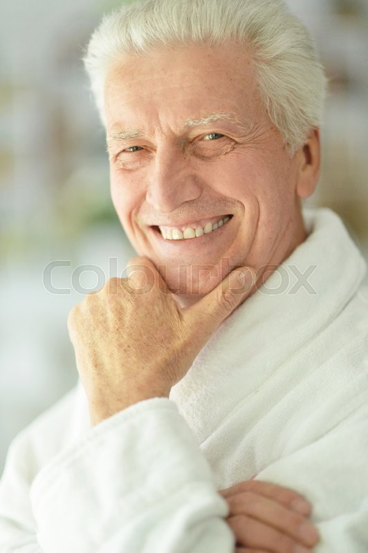 Stock image of 'happy Senior man  at home in a bathrobe'