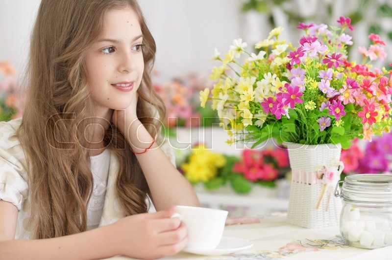 Stock image of 'Portrait of a beautiful little girl drinking tea'