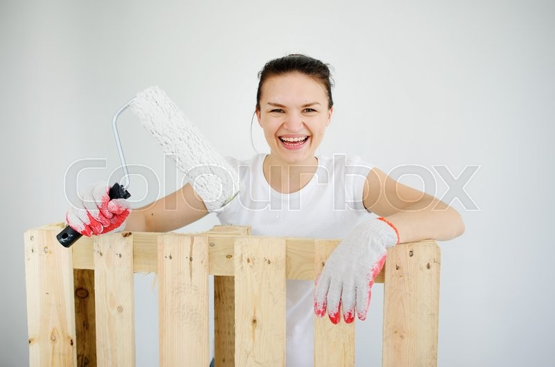 Stock image of 'The cheerful young woman leans against a wooden pallet. Her hands in working gloves. She holds the roller for coloring. The woman looks in a chamber and laughs. On a white background of a wall.'